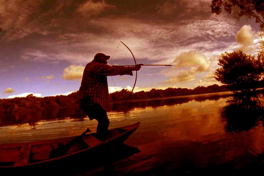 men-canoe-sunset-amazon forest-archery